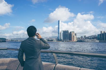 Молодой азиатский бизнес красивый улыбается, используя свой смартфон. Портрет азиатских деловой человек, используя смарт-телефон на открытом воздухе с Гонконгом делового района фон