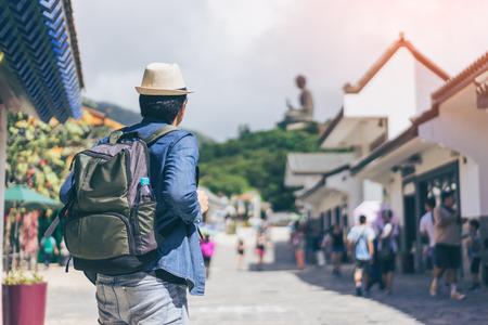Young man traveler is visiting at The enormous Tian Tan Buddha at Po Lin Monastery in Hong Kong.