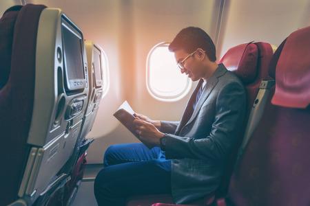Молодой азиатский деловой человек улыбается и читает книгу в самолете.