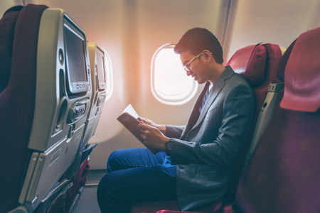 Young asian business man smiling and reading a book in airplane.