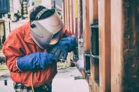 Работник сварщика ремонтирует поврежденную контейнерную стену, промышленную сварку на заводе. Рабочий ремонт контейнера коробки газовой резки и сварки тяжелой работы. Работник при сварке дуговой сваркой Фото со стока