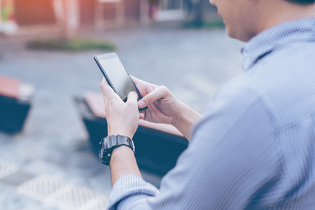 Young asian handsome businessman concentrated while reading his smartphone. Portrait of asian business man reading message with smart phone in outdoor. Фото со стока