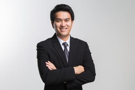 Young asian handsome businessman in black suit smiling on white background. Portrait of young asian business man.
