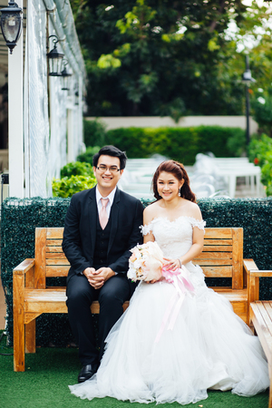 The bride and groom sitting on the chair in the garden background. Asian wedding couple on the chair in the garden background.