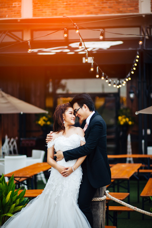 The bride and groom sweet on restaurant background. Asian wedding couple on bar restaurant background. 스톡 콘텐츠