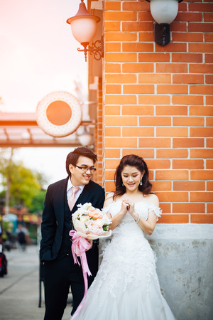 The bride and groom smiling together and give flowers in old town background. Asian wedding couple  smiling together and give flowers in old town background.
