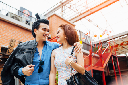 Happy young asian couple in love smiling together and hug on Japan background