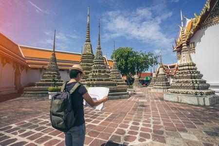 Молодой человек путешественник с рюкзаком и шляпой, глядя на карту в Wat Pho в Бангкоке Таиланд. Путешествие в Бангкок Таиланд