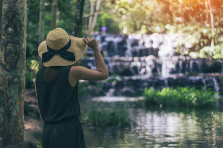 Young woman traveler and freedom. Young woman in hat with rucksack enjoying tropical waterfall view.