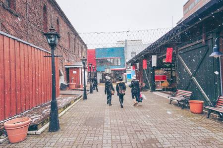Traveler walking with happinest into the historic Red Brick Warehouses with snow in winter season at Hakodate, Hokkaido, Japan Stock Photo