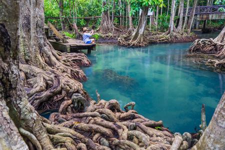 Женщина-хипстер, сидящая на деревянном мосту в джунгли, Tha pom mangrove forest, Изумрудный бассейн в мангровом лесу в Краби в Таиланде. Красивые женщины использовали смартфон сфотографировать изумрудный бассейн