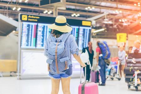 Чемодан и шляпа в зале вылета международного аэропорта, самолет в фоновом режиме, концепция путешественника, багаж и шляпа путешественника в зоне ожидания терминала аэропорта, фокус на багаже