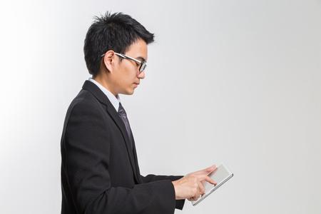 Молодой азиатский красивый бизнесмен, используя его планшет на белом backgrond. Фото со стока
