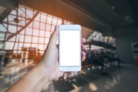 Рука человека показывает мобильный смартфон с белым экраном в вертикальном положении, размытым или Defocus аэропорта с старинным тоном. - шаблон макета и обтравочный контур
