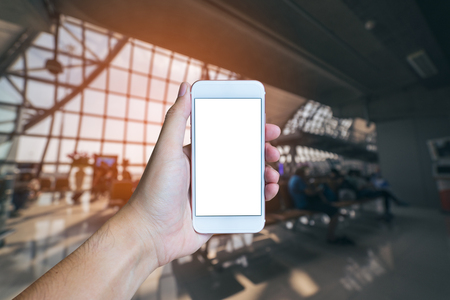 Mans hand shows mobile smartphone with white screen in vertical position, Blurred or Defocus the airport with vintage tone. - mockup template and clipping path