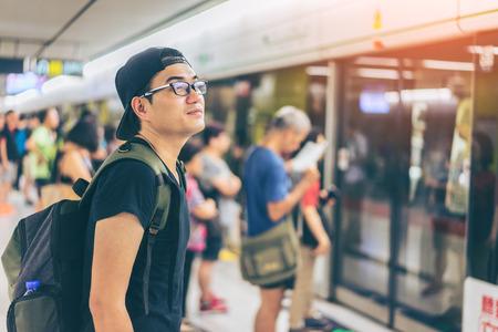 Молодой азиатский путешественник ждет транспорта под землей в Гонконге MTR