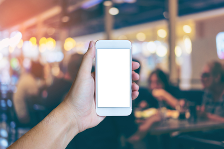 Mans hand shows mobile smartphone with white screen in vertical position,  Blurred or Defocus image of Restaurant or Cafeteria for use as Background vintage tone. - mockup template and clipping path