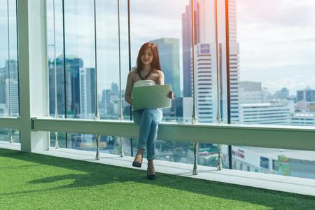 Красивая молодая женщина Азии использует ноутбук и улыбается, сидя на лестнице Фото со стока