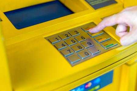 Человек, закрывающий руки, вводя свой ПИН в банкомате