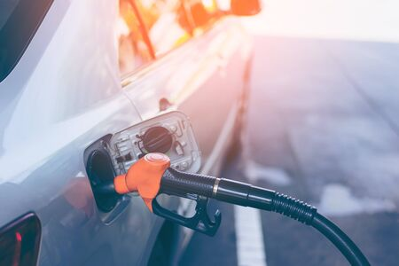 Газовое сопло перекачивает газ в серый блондин автомобиль, чтобы заполнить машину топливом. Насос бензоколонки.