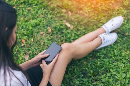 Красивая молодая женщина Азии улыбается, читая ее смартфон в саду. Портрет азиатских женщин, чтение сообщения с смарт-телефон в парке на открытом воздухе. Фото со стока