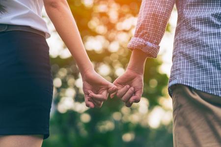 Молодая пара любви, ходить в Осенний парк, взявшись за руки, глядя на закат. Молодая пара любви розовое обещание или мизинец клянусь.