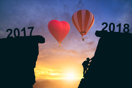 Young man climbing between 2017 and 2018 years with hot air balloon. Young climber man looking up while climbing challenging route on cliff between 2017 and 2018 years. Happy new years concept