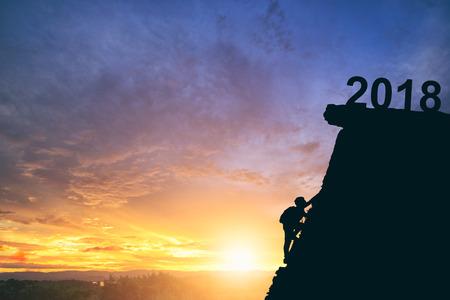 Молодой человек поднимается между 2017 и 2018 годами. Молодой человек альпинист, глядя вверх, поднимаясь сложный маршрут на скале между 2017 и 2018 годами. С Новым годом концепция