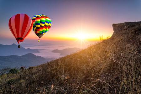 Hot air balloon with tourist is traveling into the peak of mountain and cloudscape at Phu chi fa in Chiangrai Provice, Thailand. Beautiful hot air balloon and mist at sunrise. Traveler concept