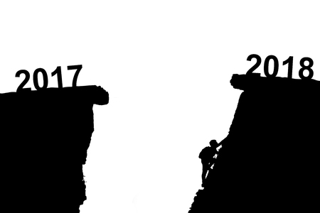 Young man climbing between 2017 and 2018 years. Young climber man looking up while climbing challenging route on cliff between 2017 and 2018 years. Happy new years concept isolated on white background 版權商用圖片