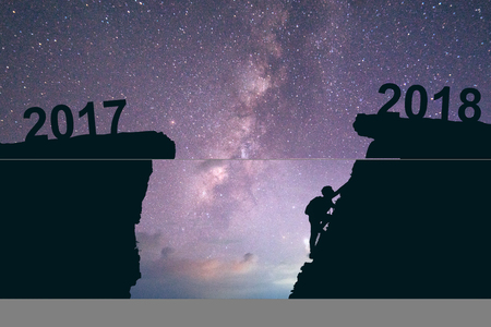 Young man climbing between 2017 and 2018 years. Young climber man looking up while climbing challenging route on cliff between 2017 and 2018 years. Happy new years concept Milky way background