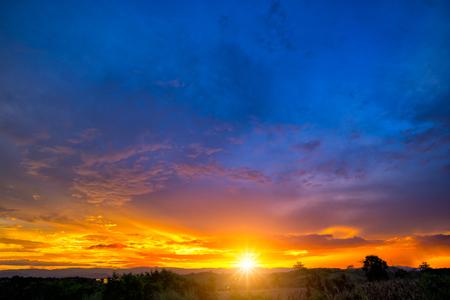 Естественный закат Восход солнца над полем или лугом. Яркое драматическое небо и темное основание. Пейзаж сельской местности под живописным красочным небом на закате Рассвет восход солнца. Солнце над горизонтом, горизонт. Теплые цвета.