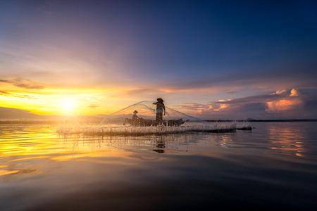 Азиатские рыболовные сети рыбака на лодке ловят рыбу на озере утром в Таиланде Фото со стока