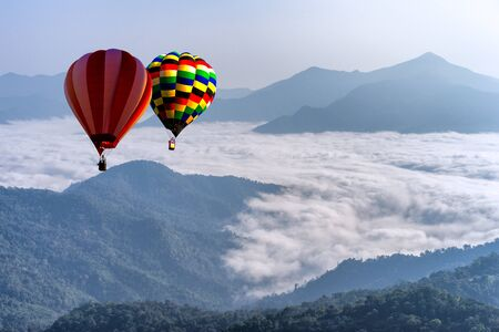 Hot air balloon with tourist is traveling into the peak of mountain and cloudscape at Doi Pha Tang in Chiangrai Provice, Thailand. Beautiful hot air balloon and mist at sunrise. Traveler concept