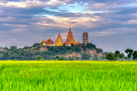 Sunset scence of Wat Tham Sua Temple with rice fields in Kanchanaburi Province, Thailand. 版權商用圖片
