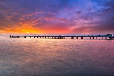 Деревянный мост в море на закате. Деревянный мост