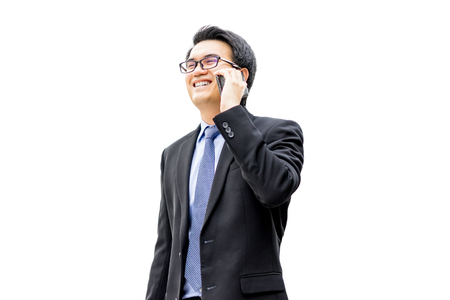 Closeup portrait of asian handsome business man using cell phone, smiling, isolated on a white background