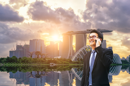 Portrait of asian handsome business man using cell phone, smiling, Singapore downtown business district background.