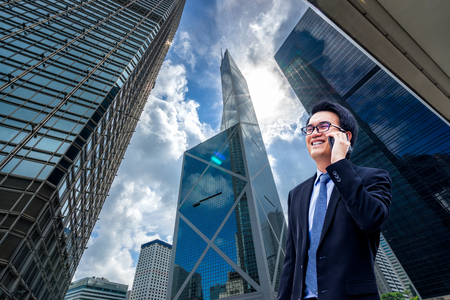 Portrait of asian handsome business man using cell phone, smiling, Hong Kong downtown business district background. 版權商用圖片