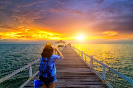 Молодая женщина путешественник, стоя на деревянный мост в море на закате Фото со стока