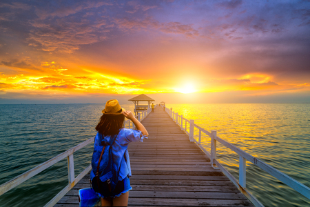 Young woman traveler standing on wooden bridge in the sea at sunset scence