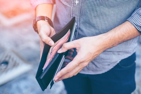 Человек, стоящий черный кошелек с деньгами Фото со стока