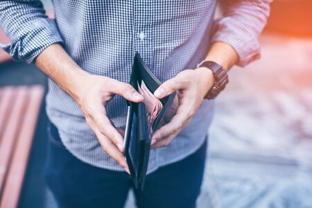 Man standing holding black wallet full of money 版權商用圖片