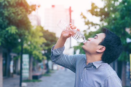 Young asian handsome business man drinking water from bottle in a park Stock Photo