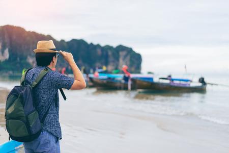 Молодой человек путешественник с зеленым рюкзаком и шляпу, глядя на море с давно лодку Таиланд фон от Ao Nang Beach Краби. Путешествие в Краби, Таиланд, Концепция летнего путешественника