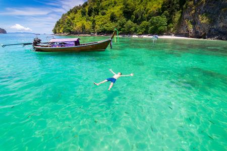 Плавание путешественника-молодого человека, окруженного рыбой с длинной тайской лодкой в Краби Море в Андаманском море, Таиланд
