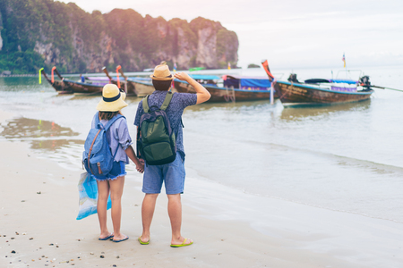 Young love couple traveler with backpack and hat holding map at the sea with long boat thailand background from Ao Nang Beach Krabi. Traveling in Krabi Thailand , Traveler summer concept 版權商用圖片