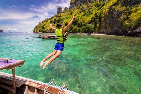 Путешественник молодого человека прыгает в море, образуя длинную тайскую лодку на острове цыпленка возле пляжа Рейлей в провинции Краби, Таиланд в Андаманском море на юге Таиланда.