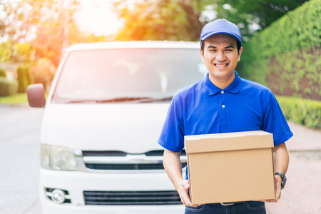 Delivery concept - Smiling happy young asian handsome man  postal delivery courier man in front of cargo van delivering package holding box with service mind and blue uniform