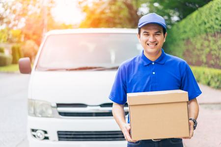Concept de livraison - Sourire heureux jeune bel homme bel homme de courrier postal de livraison en face de la fourgonnette de livraison de colis tenant la boîte avec l'esprit de service et uniforme bleu